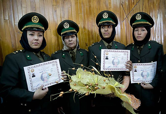 Newly trained female officers of the Afghan National Army show their certificates during their graduation ceremony at National Army's training center in Kabul, Afghanistan, on Septemb