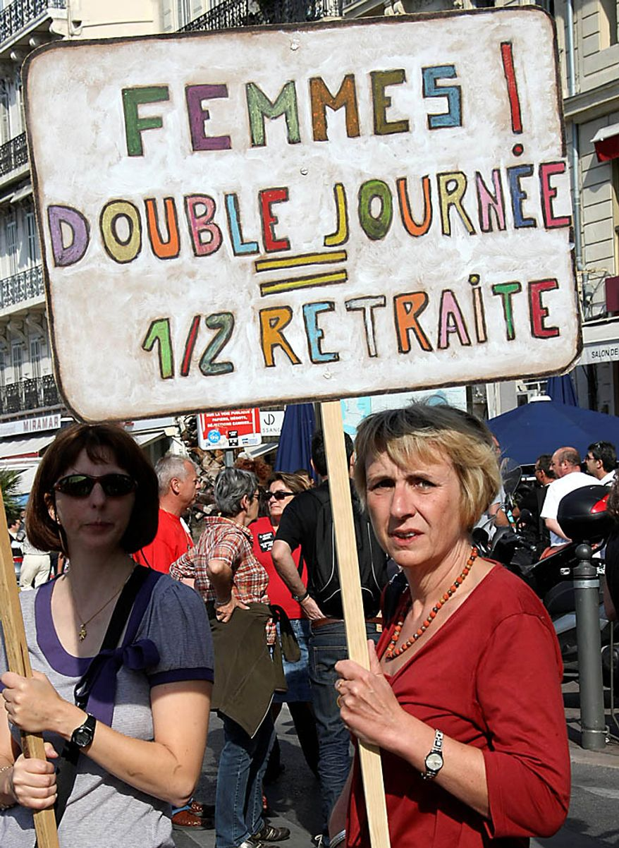 """Women holding a placard reading """"Women! Double day, Half pension"""" during a protest, in Marseille, southern France, Thursday Sept. 23, 2010. French commuters squeezed onto limited trains or fought for rare parking spots Thursday as a second round of strikes against President Nicolas Sarkozy's plan to raise the retirement age to 62 hobbled trains, planes and schools across the country. (AP Photo/Claude Paris)"""