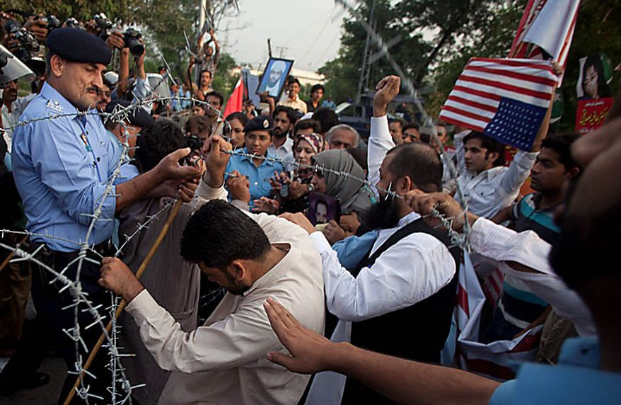 Pakistani police block protesters trying to get to the U.S. Embassy in Islamabad, Pakistan, to condemn the sentencing in New York of Pakistan-born scientist Aafia Siddiqui on Thursday, Sept. 23, 2010. (AP Photo/B.K. Bangash)