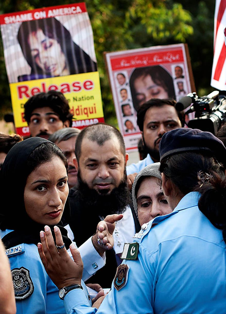 Police officers block Pakistani protesters from reaching the U.S. Embassy in Islamabad, Pakistan, on Thursday, Sept. 23, 2010, as they demonstrate against the sentencing of Aafia Siddiqui, a Pakistani scientist convicted in New York of trying to kill U.S. agents and military officers. (AP Photo/B.K. Bangash)