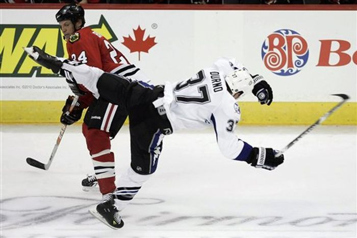 Chicago Blackhawks' Nick Boynton (24) checks Tampa Bay Lightning's Chris Durno (37) during the second period of their preseason NHL hockey game in Winnipeg, Manitoba, Wednesday, Sept. 22, 2010. (AP Photo/The Canadian Press, John Woods)