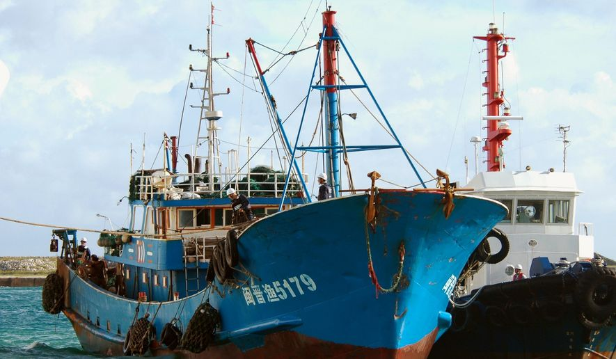 In this photo from Sept. 8, 2010, a Chinese fishing boat (left), which was involved in a collision near disputed islands, arrives at a port on Ishigaki island, Okinawa prefecture, southwestern Japan. Japanese prosecutors decided Sept. 24, 2010, to release the captain of the Chinese fishing boat, whose detention raised tensions between the Asian neighbors. (Associated Press/Kyodo News)