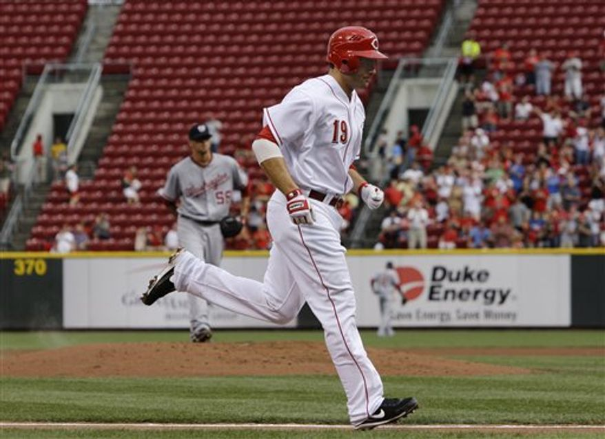 This July 20, 2010, photo shows Cincinnati Reds' Joey Votto (19)  rounding the bases after hitting a three-run home run off Washington Nationals starting pitcher Luis Atilano, left, in the first inning of a baseball game, in Cincinnati. The Reds are on the verge of the playoffs, but they can't come close to filling their ballpark. (AP Photo/Al Behrman)