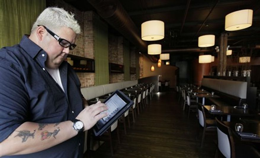 This Tuesday, Sept. 14, 2010 photo shows chef Graham Elliot of Graham Elliot restaurant as he poses in the dining room of his restaurant in Chicago. Elliot frequently tweets his opinions about topics other than his restaurant or cooking, from current events to fantasy football picks. He even uses Twitter to let his followers make decisions about the music the restaurant plays.    (AP Photo/M. Spencer Green)