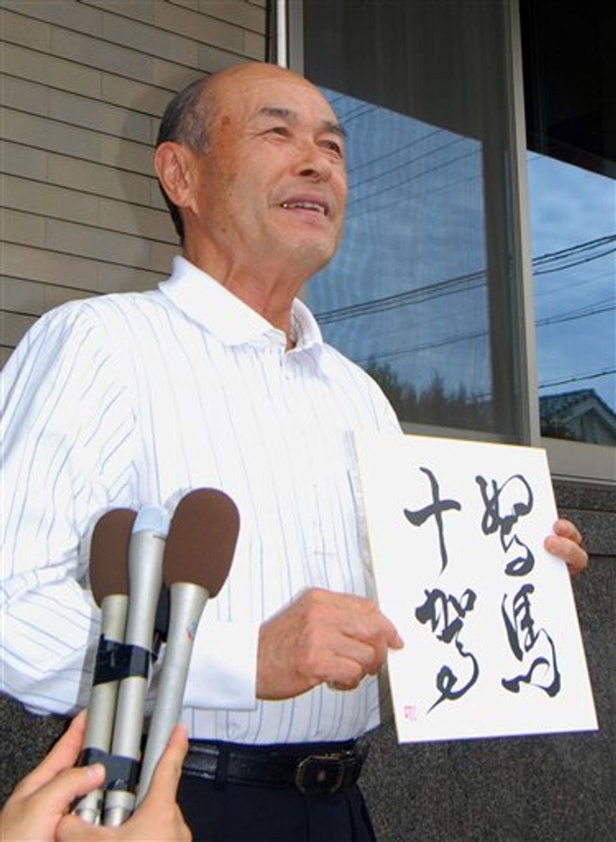 "Nobuyuki Suzuki, the father of Seattle Mariners Ichiro Suzuki who became the first Major League Baseball player with 10 consecutive 200-hit seasons, speaks to reporters with his calligraphy of an idiom by third century BC Chinese Confucian philosopher Xun Zi in Toyoyama in Aichi Prefecture, central Japan, Friday, Sept. 24, 2010. Nobuyuki said his son's achievements are the result of a lot of hard work while showing the Chinese idiom meaning: ""any packhorse that runs slow can run fast and overtake a fine horse if it keeps running with a cart for 10 days."" (AP Photo/Kyodo News)"