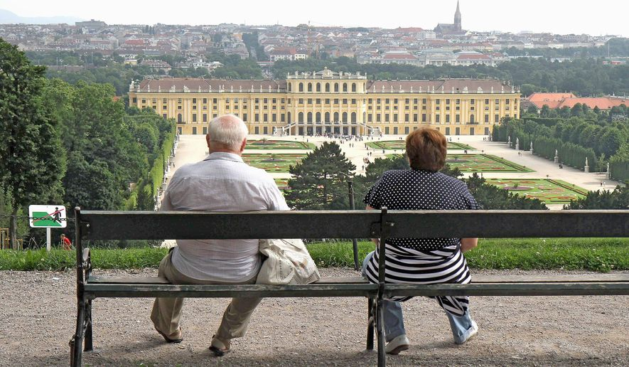 Two people look down on the former imperial Schoenbrunn Palace in Vienna, Austria, in June. The palace, once lived in by members of the Habsburg dynasty when it ruled the Austro-Hungarian Empire, isn't just a museum. It is now home to ordinary Austrians. (Associated Press)