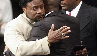 Bishop Eddie Long (left) embraces an attendee at services at the New Birth Missionary Baptist Church outside Atlanta on Sunday, Sept. 26, 2010. Bishop Long, the pastor of the Georgia megachurch, who is accused of luring young men into sexual relationships, told his congregation of thousands that all people must face painful and distasteful situations. (AP Photo/John Amis, Pool)