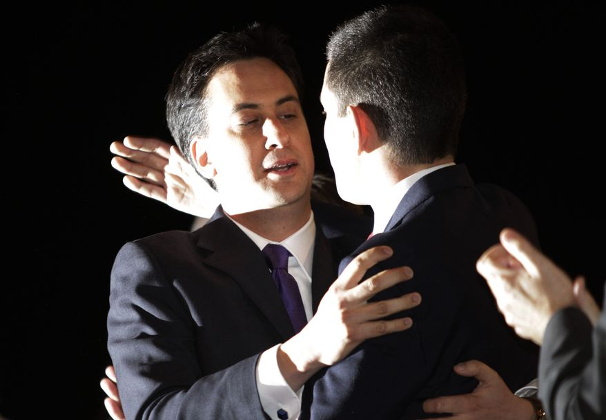 Ed Miliband (left), newly-elected leader of Britain's opposition Labor Party, embraces brother David Miliband, who was also a candidate for the top party post, following the announcement of his selection at the start of the party's annual conference in Manchester, England, on Saturday, Sept. 25, 2010. (AP Photo/Lefteris Pitarakis)