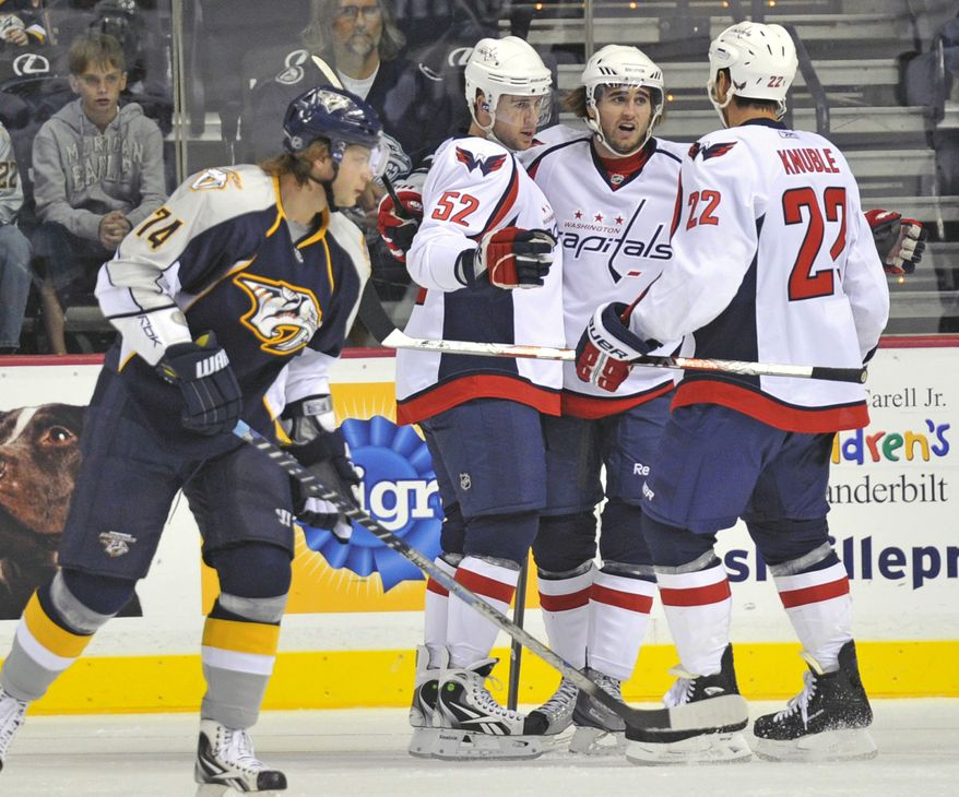 ASSOCIATED PRESS Nashville Predators left wing Sergei Kostitsyn (74) skates by as Washington Capitals defenseman Mike Green (52) and forward Mike Knuble (22) celebrate a goal with forward Francois Bouchard during the first period of a preseason NHL hockey game in Nashville, Tenn., Saturday, Sept. 25, 2010.