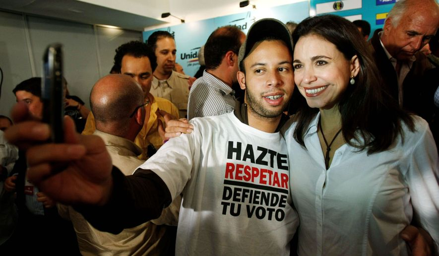 RISING STAR: Independent activist Maria Corina Machado poses with a supporter Monday after being elected to Venezuela's National Assembly. She has been touted as a challenger to President Hugo Chavez. (Associated Press)