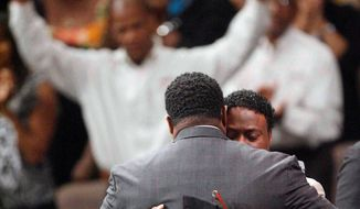Bishop Eddie Long (right), embraces a friend at a Sunday service in Atlanta. He did not directly deny accusations of sexually seducing young men. (Associated Press)