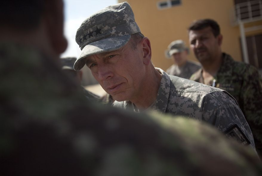 In this photo reviewed by the U.S. military, the top American commander in Afghanistan Gen. David Petraeus speaks with Afghan military personnel during a tour of the U.S. run Parwan detention facility near Bagram north of Kabul, Afghanistan on Monday Sept. 27, 2010. (AP Photo/David Guttenfelder)