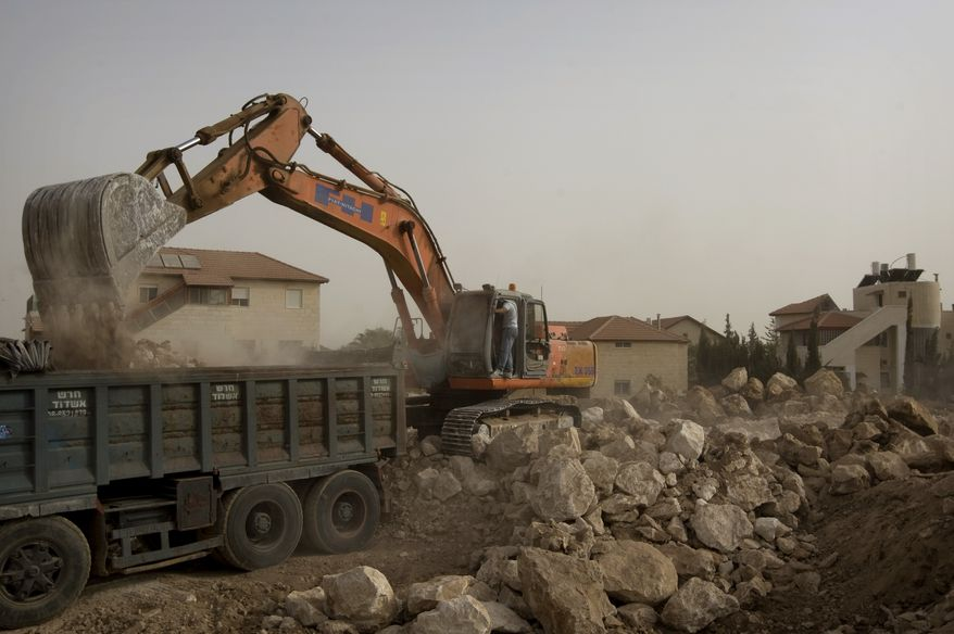 """A bulldozer works at a construction site in the Jewish settlement of Adam outside Jerusalem on Sunday, Sept. 26, 2010. With a midnight deadline looming, Israeli Prime Minister Benjamin Netanyahu on Sunday called on West Bank settlers to """"show restraint"""" after the end of a government-ordered construction slowdown, attempting to lower tensions with the Palestinians and prevent a breakdown in newly relaunched Mideast talks. (AP Photo/Sebastian Scheiner)"""