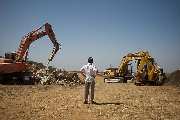 A Jewish settler boy looks at earth-moving equipment working at a construction site in the West Bank Jewish settlement of Ariel, Monday, Sept. 27, 2010. Senior Palestinian official Yasser Abed Rabbo said Monday that President Mahmoud Abbas remains ready to walk out on Mideast peace talks if Israel resumes construction in its West Bank settlements now that building restrictions have expired. (AP Photo/Ariel Schalit)
