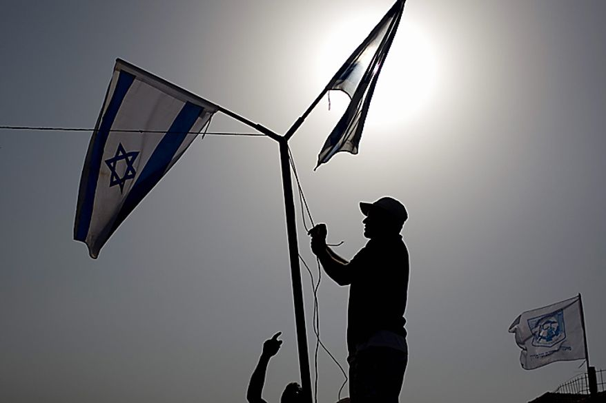 "Jewish settlers hang Israeli flags during a cornerstone laying ceremony for a daycare center in the West Bank Jewish settlement of Kiryat Netafim, Sunday, Sept. 26, 2010. With a midnight deadline looming, Israel's prime minister on Sunday called on West Bank settlers to ""show restraint"" after the end of a government-ordered construction slowdown, attempting to lower tensions with the Palestinians and prevent a breakdown in newly relaunched Mideast talks. (AP Photo/Ariel Schalit)"