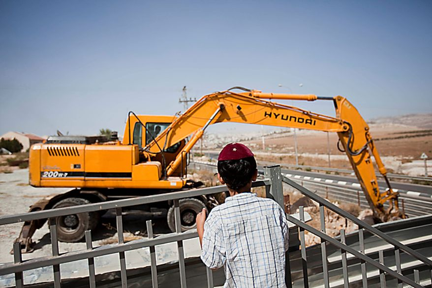 ** FILE ** A Jewish settler boy looks at earth-moving equipment working at a construction site in the West Bank Jewish settlement of Adam, near Ramallah, on Monday, Sept. 27, 2010. (AP Photo/Bernat Armangue)