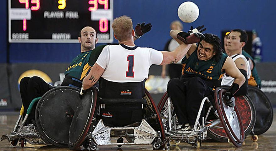 United States' Chance Sumner (1) passes to teammate Will Groulx, right, as Australia's Bryce Alman, left, and Nazim Erdem (2) defend during the gold medal match at the World Wheelchair Rugby Championships in Richmond, British Columbia, on Sunday, Sept. 26, 2010. (AP Photo/The Canadian Press, Darryl Dyck)