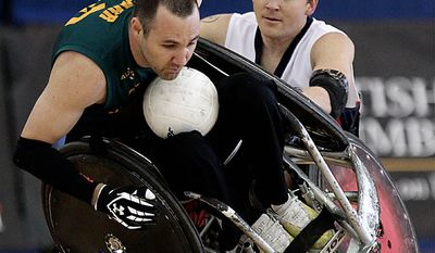 Australia's Cameron Carr, left, is knocked over by USA's Andy Cohn during the gold medal match at the World Wheelchair Rugby Championships in Richmond, British Columbia on Sunday Sept. 26, 2010. (AP Photo/The Canadian Press, Darryl Dyck)