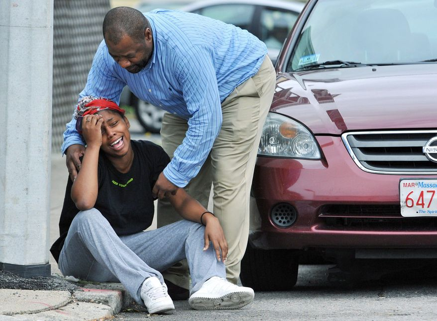 A man comforts a grieving woman near the scene of the shooting, which occurred in Matapan, a neighborhood that had 14 homicides in 2010 before Tuesday, compared to six in the same time last year. (Associated Press)