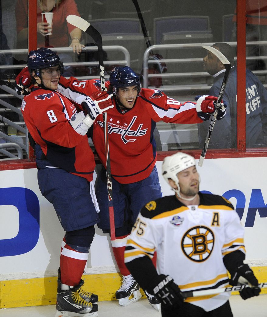 ASSOCIATED PRESS Washington Capitals' Mathieu Perreault, back right, celebrates his goal with Alex Ovechkin (8), of Russia, as Boston Bruins' Mark Stuart (45) looks on during the first period an NHL hockey preseason game Tuesday, Sept. 28, 2010, in Washington.