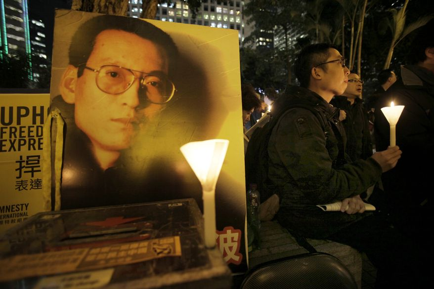 In this Jan. 12, 2010, file photo, pro-democracy protesters hold a candle light vigil as they support recently jailed mainland dissident Liu Xiaobo, shown on a poster, in Hong Kong. (AP Photo/Vincent Yu, File)