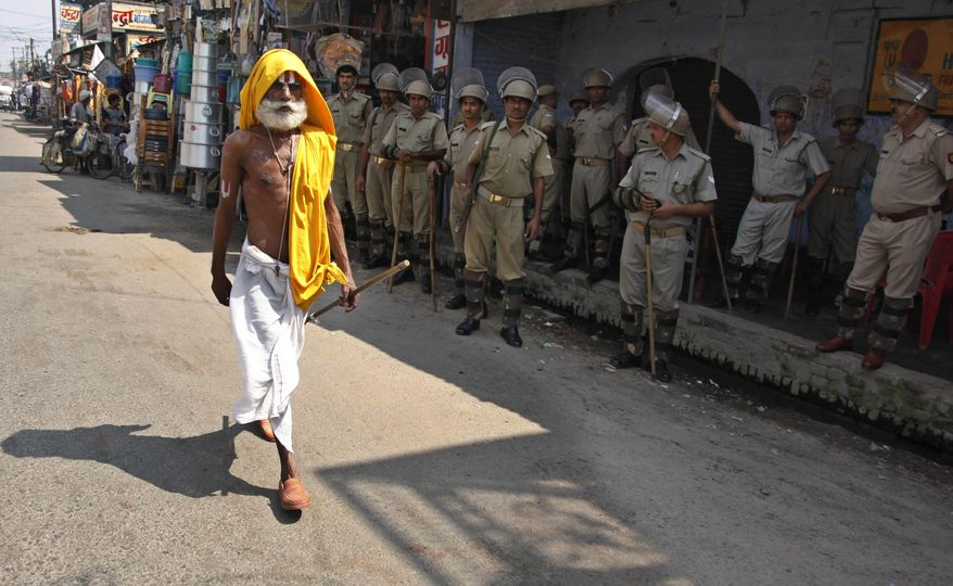 A Hindu holyman walks past Indian securitymen standing guard in Ayodhya, India, Tuesday, Sept. 28, 2010. The Indian Supreme Court rejected Tuesday a plea to delay judgment on whether Hindus or Muslims should control a disputed holy site, clearing the way for a verdict in the explosive case later this week. (AP Photo/Rajesh Kumar Singh)