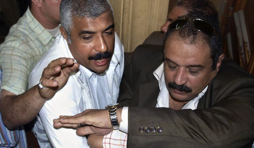In this Thursday, May 21, 2009, file photo, Egyptian policemen guard Hisham Talaat Moustafa, an Egyptian real estate mogul and lawmaker, center-left, as he leaves a court in Cairo. In a case which has captivated the Arab public, an Egyptian court has handed the billionaire tycoon a lighter sentence of just 15 years after an earlier trial sentenced him to death for paying a retired Egyptian police officer to kill his popstar lover, Lebanese singer Suzanne Tamim, it was reported on Tuesday, Sept. 28, 2010. (AP Photo/Nasser Nouri, File)