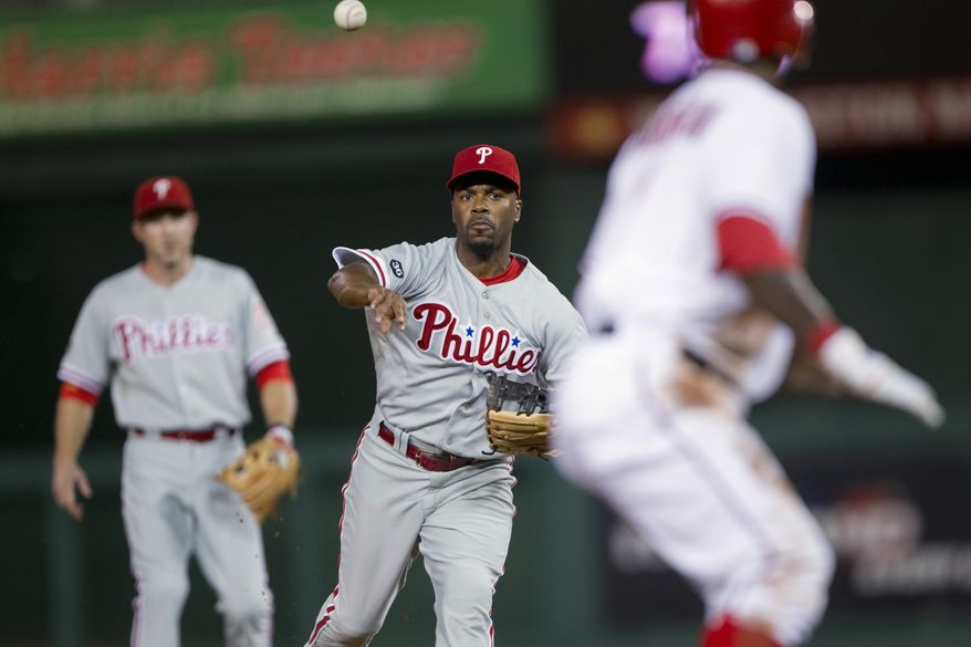ASSOCIATED PRESS Philadelphia Phillies  shortstop Jimmy Rollins, center, throws during a rundown on Washington Nationals' Nyjer Morgan, right, during the first inning of a baseball game Tuesday, Sept. 28, 2010, in Washington. At left is Phillies second baseman Chase Utley. Morgan ended up advancing to third on the play.