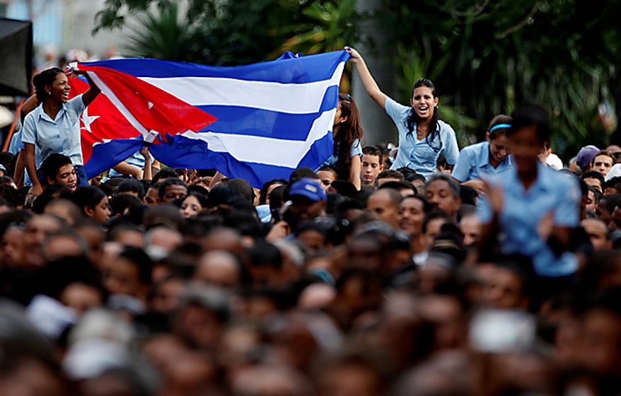 Students wave a Cuban flag during a speech delivered by Cuba's leader Fidel Castro as part of the celebrations of the 50th anniversary of the Committee for the Defense of the Revolution, CDR, in Havana, Cuba, Tuesday, Sept. 28, 2010. (AP Photo/Javier Galeano)