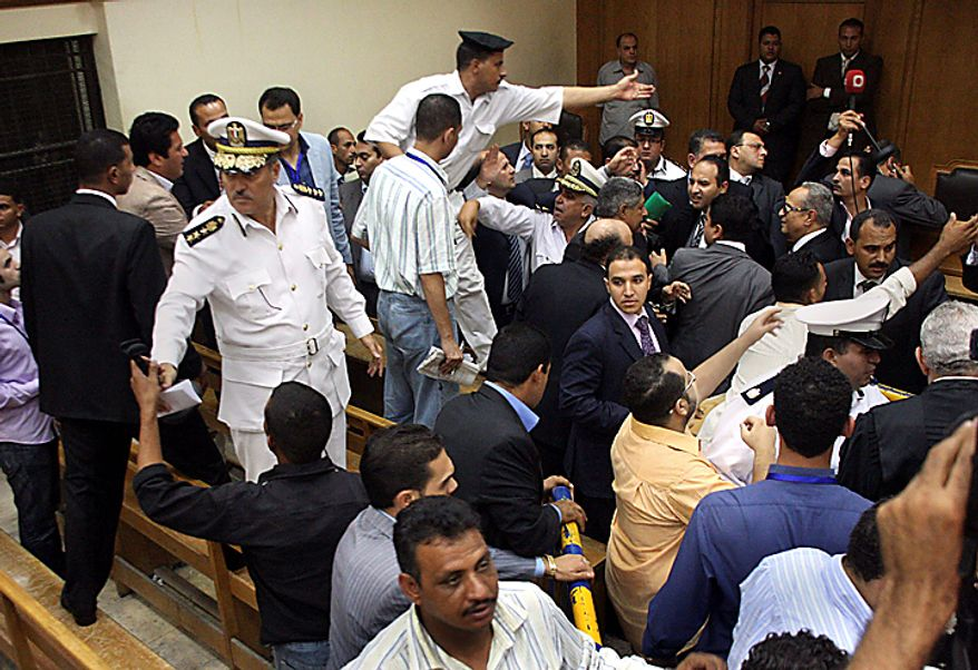 Egyptian policemen restore order, Tuesday, Sept. 28, 2010 after the verdict on Hisham Talaat Moustafa, an Egyptian real estate mogul and lawmaker, at a court in Cairo, Egypt. In a case which has captivated the Arab public, the court has handed billionaire tycoon Hisham Talaat Moustafa a lighter sentence of just 15 years after an earlier trial sentenced him to death for paying a retired Egyptian police officer to kill his pop star lover, Lebanese singer Suzanne Tamim. (AP Photo/Maher Malak)