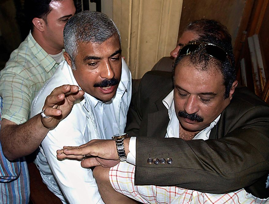 In this Thursday, May 21, 2009 file photo, Egyptian policemen guard Hisham Talaat Moustafa, an Egyptian real estate mogul and lawmaker, centre-left, as he leaves a court in Cairo, Egypt. In a case which has captivated the Arab public, an Egyptian court has handed billionaire tycoon Hisham Talaat Moustafa a lighter sentence of just 15 years after an earlier trial sentenced him to death for paying a retired Egyptian police officer to kill his popstar lover, Lebanese singer Suzanne Tamim, it was reported on Tuesday, Sept. 28, 2010.  (AP Photo/Nasser Nouri, File)