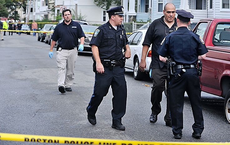 Boston police speak near the scene of a shooting in Boston, Tuesday, Sept. 28, 2010, following an early morning shooting in which five people including a toddler were shot in the Mattapan neighborhood of Boston. (AP Photo/Josh Reynolds)