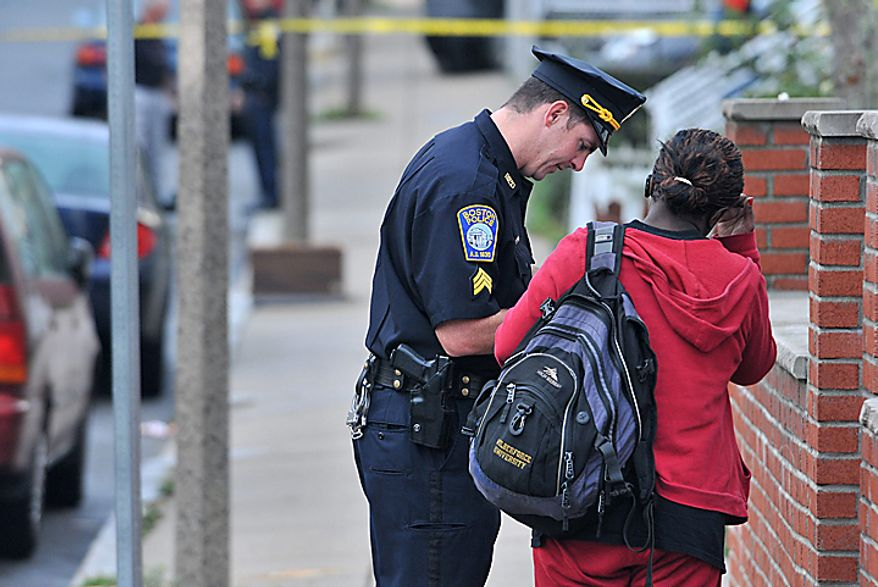 A Boston police officer speaks to a neighbor, Tuesday, Sept. 28, 2010, near the scene of an early morning shooting in which five people including a toddler were shot in the Mattapan neighborhood of Boston. (AP Photo/Josh Reynolds)