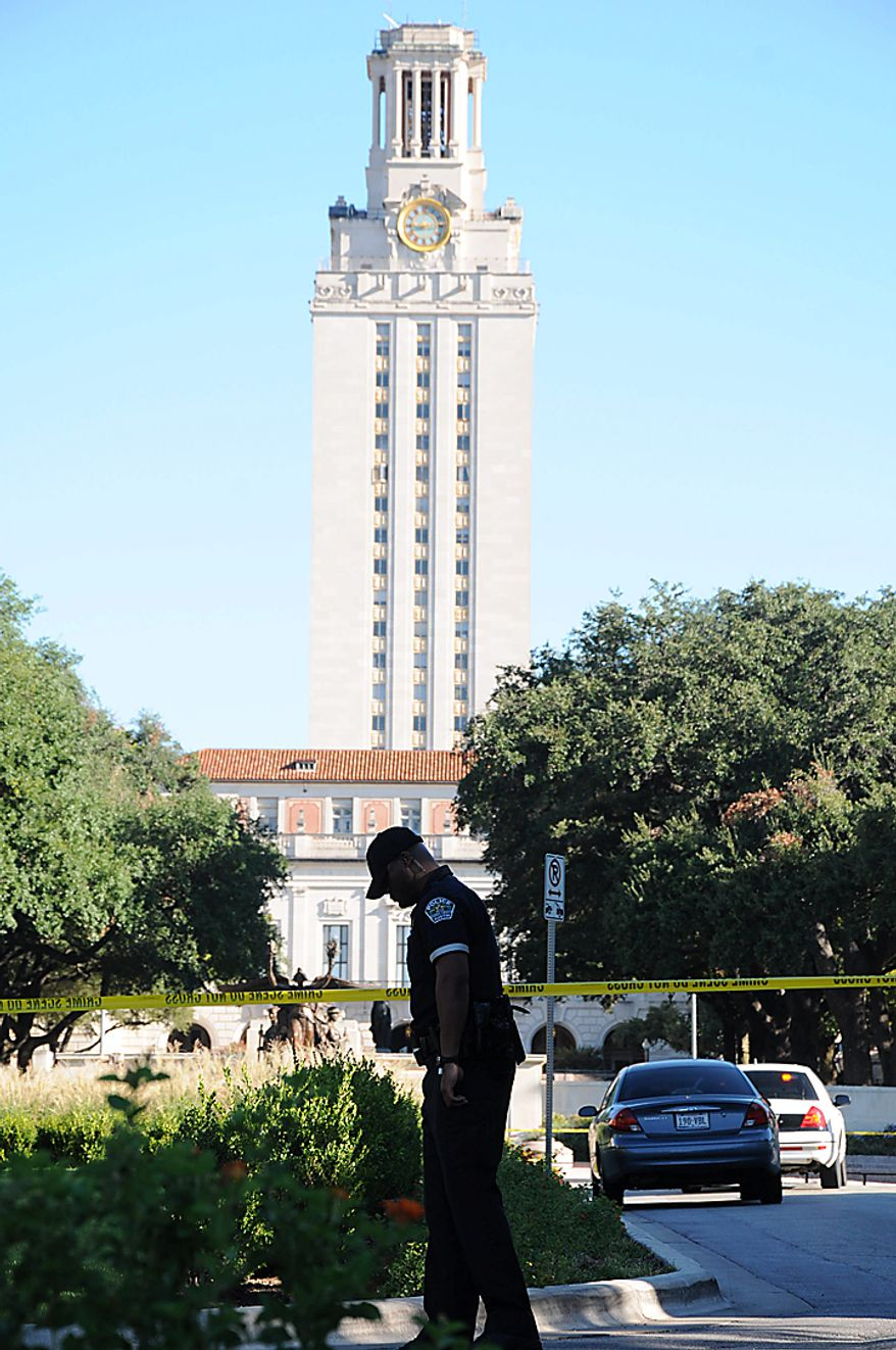 A police officer patrols  the University of Texas campus in Austin early Tuesday morning Sept. 28, 2010 after a gunman opened fire at the Perry-Castaneda Library. A gunman opened fire Tuesday inside a University of Texas campus library then fatally shot himself, and police are searching for a possible second suspect, university police said. The UT clock tower is seen in the background. (AP Photo/The Daily Texan, Derek Stout)