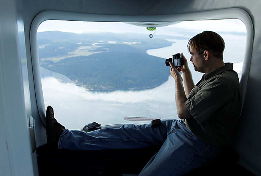 "Brian Hall, owner of the Zeppelin airship ""Eureka, "" and founder of Airship Ventures, Inc., takes photographs as he rides next to the airship's rear window during a flight dedicated to whale research, near San Juan Island, Wash., Wednesday, Sept. 8, 2010. Hall is also the CEO of the software company Mark/Space Inc. (AP Photo/Ted S. Warren)"