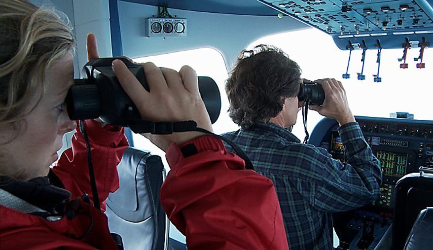 """In this still image taken from video, Erin Heydenreich, left, of the Center for Whale Research, and Brad Hanson, a NOAA wildlife biologist, right, view killer whales from the air aboard the Zeppelin airship """"Eureka,"""" near San Juan Island, Wash., Wednesday, Sept. 8, 2010. (AP Photo/Ted S. Warren)"""