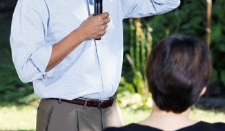 ASSOCIATED PRESS 'BACK-AND-FORTH': President Obama answers a question Wednesday during a discussion with neighborhood families in the backyard of a home in Des Moines, Iowa.