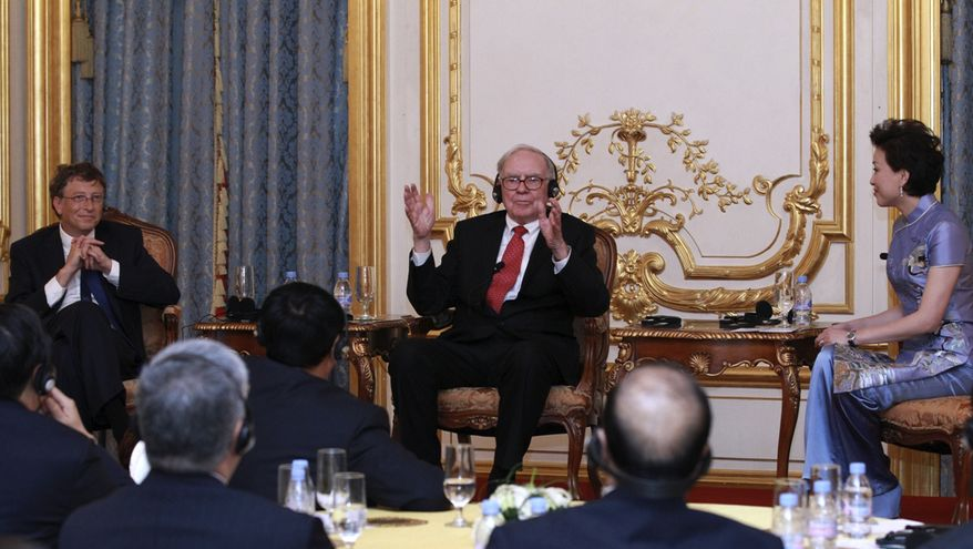 Bill Gates, left, and Warren Buffett, center, talk with some of China's richest people to promote philanthropy during a dinner and reception Wednesday Sept. 29, 2010 in Beijing. (AP Photo/Xinhua, Pang Xingdong)
