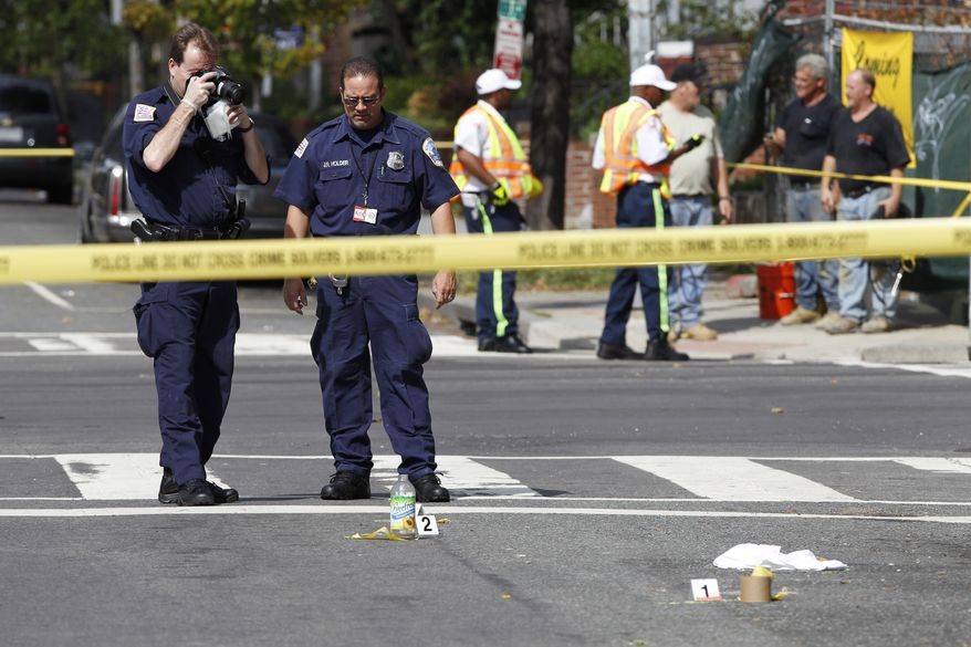Washington Police officers collect evidence at a crime scene on 13th and U Street in Northwest Washington, Tuesday, Sept. 28, 2010. Police are searching for a suspect in a shooting and subsequent car crash that left one person dead and two others wounded on Washington's popular U Street corridor (AP Photo/Manuel Balce Ceneta)