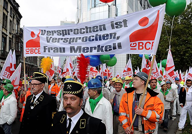 "Protestors carry a banner which reads ""A promise is a promise, Mrs. Merkel"" during a trade demonstration in Brussels, Belgium on Wednesday, Sept. 29, 2010. (AP Photo/Geert Vanden Wijngaert)"