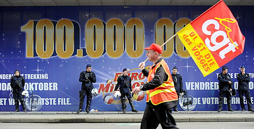A demonstrator holds a banner as he marches down a main boulevard in Brussels, Belgium on Wednesday, Sept. 29, 2010. (AP Photo/Geert Vanden Wijngaert)