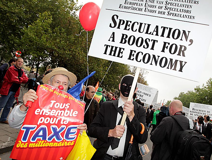 Demonstrators hold banners as they march down a main boulevard in Brussels, Belgium on Wednesday, Sept. 29, 2010. (AP Photo/Yves Logghe)