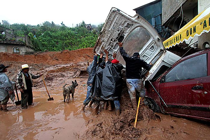 Men inspect a vehicle buried under mud after a landslide in the town of Santa Maria de Tlahuitoltepec, Mexico Tuesday Sept. 28, 2010. A mudslide first thought to have buried hundreds of people has left 11 missing and there are no confirmed dead, authorities said, backing off earlier predictions of a catastrophe in Mexico's rain-soaked southern state of Oaxaca. (AP Photo/Luis Alberto Cruz Hernandez)