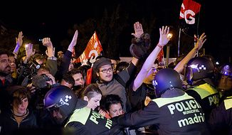 Police push back pickets outside a bus depot during a nationwide general strike organized by the Spanish unions, in Madrid, Wednesday, Sept. 29, 2010. Picketers hurled eggs at buses and blocked trucks from delivering produce to wholesale markets as Spanish workers went on a general strike Wednesday to protest austerity measures imposed by a government struggling to slash its budget deficit and overcome recession.  (AP Photo/Paul White)