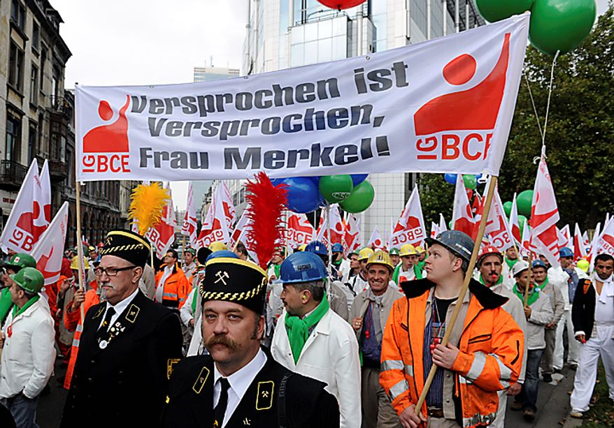 """Protestors carry a banner which reads """"A promise is a promise, Mrs. Merkel"""" during a trade demonstration in Brussels, Belgium on Wednesday, Sept. 29, 2010. (AP Photo/Geert Vanden Wijngaert)"""