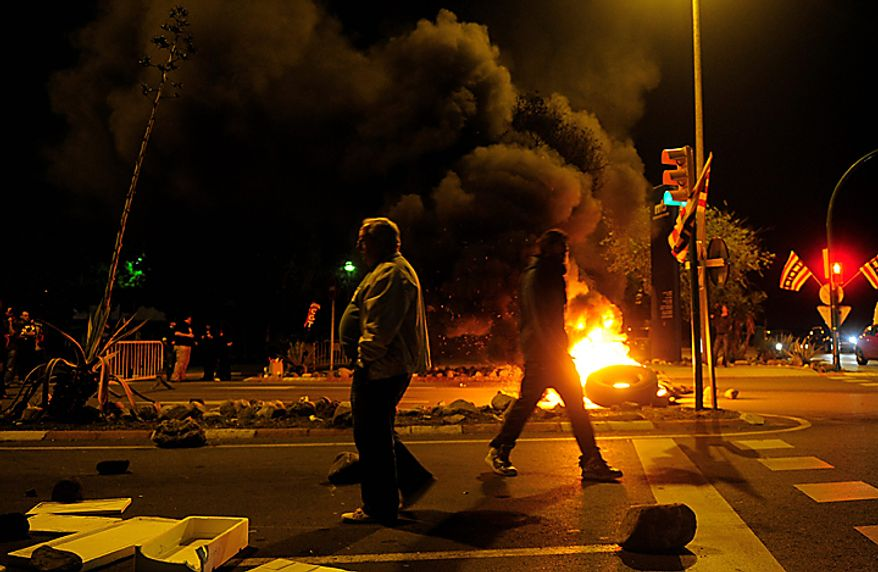 """Workers burn tires in front of """"Mercabarna (General Market) """" during a general strike in Barcelona, Spain, early Wednesday, Sept. 29, 2010 to protest the budget-slashing plans and austerity measures of governments seeking to control debt. (AP Photo/Manu Fernandez)"""