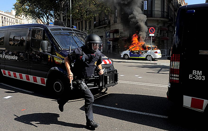 A riot police runs as a patrol police car burns during riots in Barcelona, on Wednesday, Sept. 29, 2010. Spanish workers staged a general strike Wednesday to protest austerity measures imposed by a government struggling to slash its budget deficit and overcome recession. (AP Photo/Manu Fernandez)