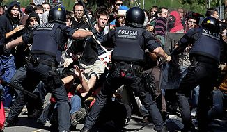 Riot police hit out at demonstrators during protests in Barcelona, Spain, Wednesday, Sept. 29, 2010. Spanish workers staged a general strike Wednesday to protest austerity measures imposed by a government struggling to slash its budget deficit and overcome recession.(AP Photo/David Ramos)