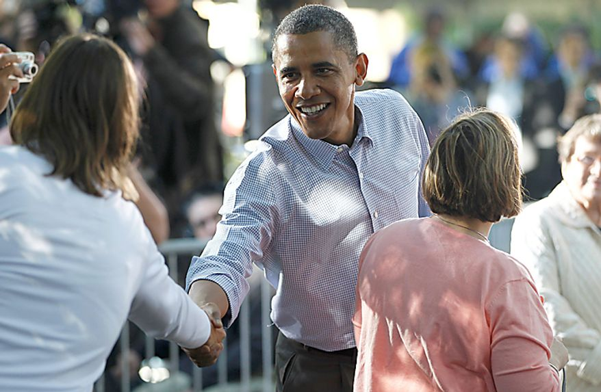 President Barack Obama greets residents during a discussion with neighborhood families in the backyard of the Clubb family in Des Moines, Iowa, Wednesday, Sept. 29, 2010. (AP Photo/Charles Dharapak)