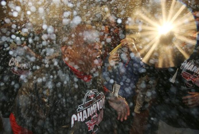 Cincinnati Reds manager Dusty Baker is sprayed with champagne after the Reds defeated the Houston Astros 3-2 in a baseball game to clinch the NL Central, Tuesday, Sept. 28, 2010, in Cincinnati. (AP Photo/Tom Uhlman)